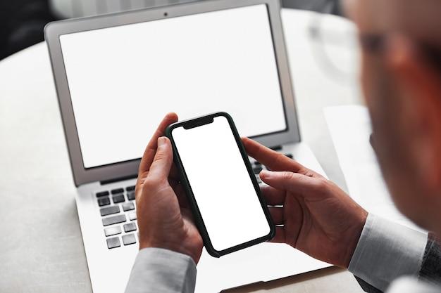 白い画面のノートパソコンの背景に白い画面の携帯電話を持っている男