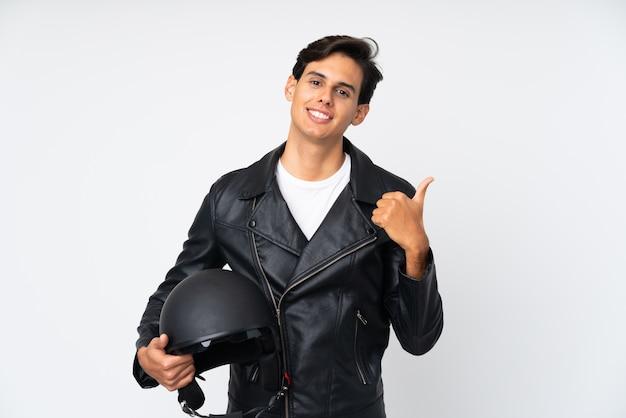 親指ジェスチャーを与える分離の白い壁にオートバイのヘルメットをかざす男