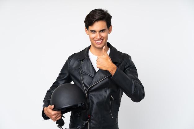 Мужчина держит мотоциклетный шлем на белой стене, давая недурно жест