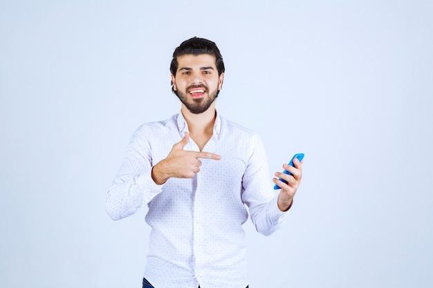 新モデルのスマートフォンを持って指さしている男