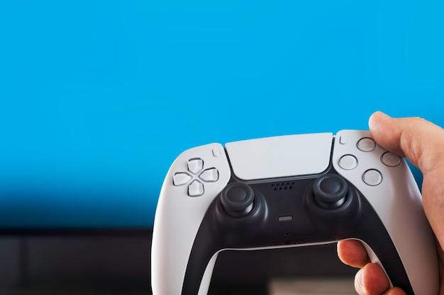 파란색 배경에 격리된 차세대 흰색 게임 컨트롤러를 들고 있는 남자. 크로마 키.