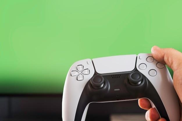 녹색 배경에 격리된 차세대 흰색 게임 컨트롤러를 들고 있는 남자. 크로마 키.
