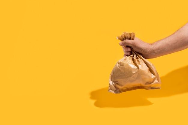노란색 배경에 종이 봉지를 들고 있는 남자