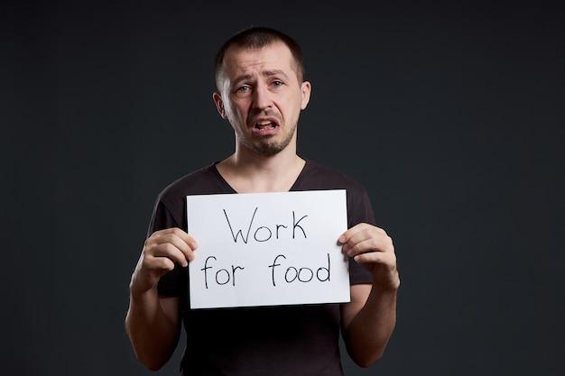 食べ物の碑文の仕事で紙シートを持っている男