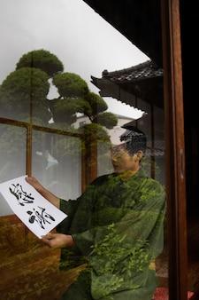 日本語の手書きの紙を持っている男