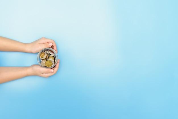 手にコインを持って貯金箱を持っている男