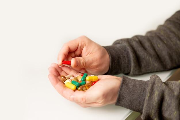 손에 알약과 비타민 더미를 들고 있는 남자