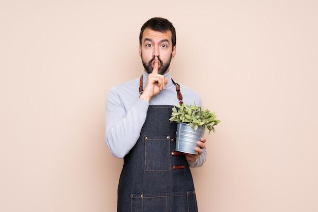 입에 손가락을 넣어 침묵 제스처의 표시를 보여주는 격리 된 배경 위에 식물을 들고 남자