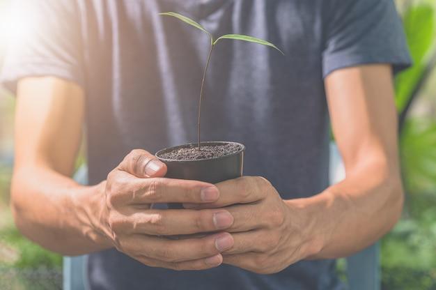 식물 냄비를 들고 남자입니다. 식물에 대한 사랑의 개념.