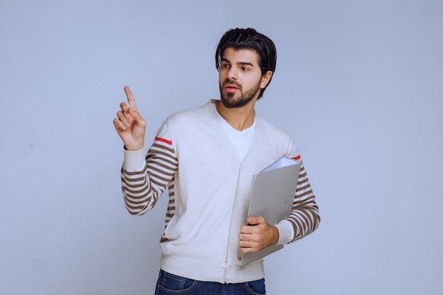 プロジェクトフォルダを保持し、上を指している男。