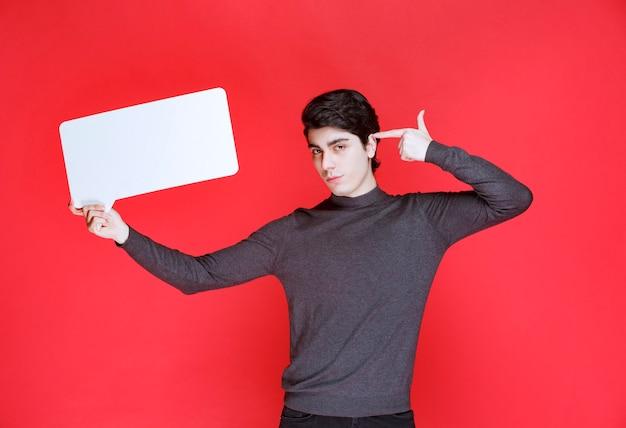 長方形のアイデアボードを持ってブレーンストーミングをしている男