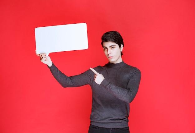長方形のアイデアボードを持って参加者を指差す男
