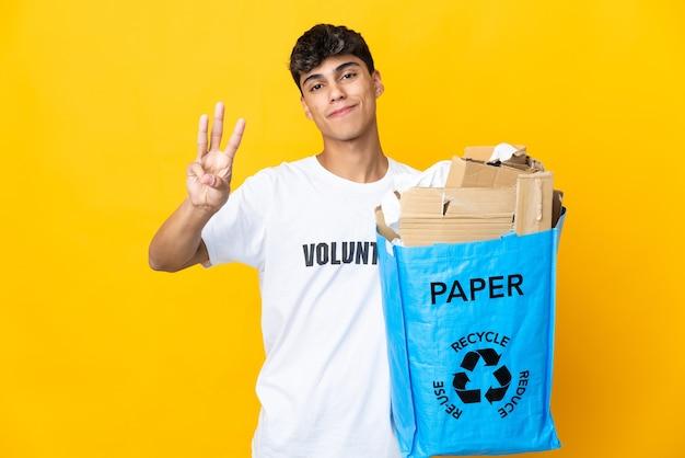 격리 된 노란색 배경 위에 재활용 종이로 가득 찬 재활용 가방을 들고 남자가 행복하고 손가락으로 세 세