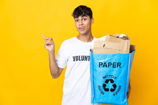 指を持ち上げながら解決策を実現しようとしている孤立した黄色の背景の上にリサイクルするために紙でいっぱいのリサイクルバッグを持っている男