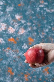 Мужчина держит в руке красное яблоко