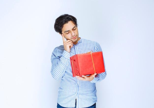 Мужчина держит красную подарочную коробку и выглядит смущенным и задумчивым. фото высокого качества