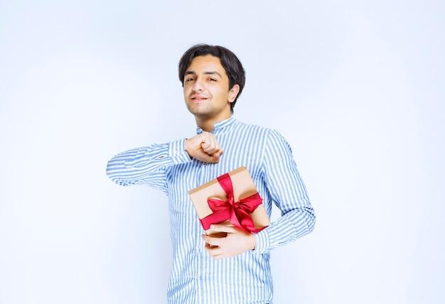 赤いリボンの段ボールのギフトボックスを持って、感謝の気持ちを表す男。高品質の写真