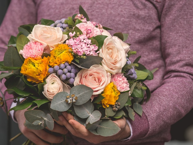 Мужчина держит романтический букет цветов смешанного выбора и готов предложить