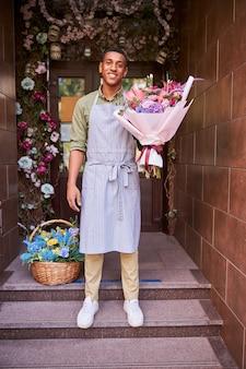 彼の足に青い花のバスケットと彼の手でバラの花束を持っている男
