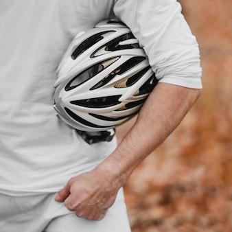 自転車用の安全ヘルメットを持っている男