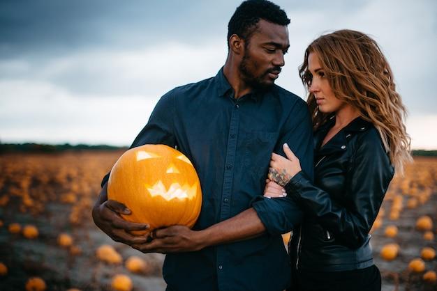 Мужчина держит страшную тыкву рядом со своей девушкой