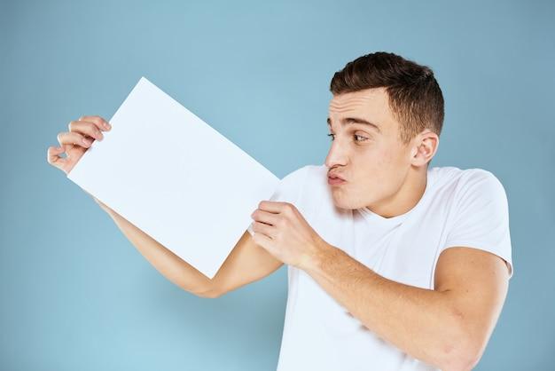 그의 손에 종이 한 장을 들고 남자 흰색 t- 셔츠 자른보기 블루.