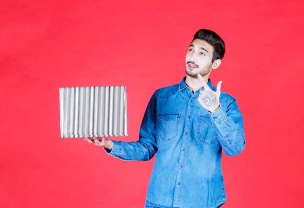 Мужчина держит серебряную подарочную коробку на красной стене и выглядит удивленным и задумчивым.