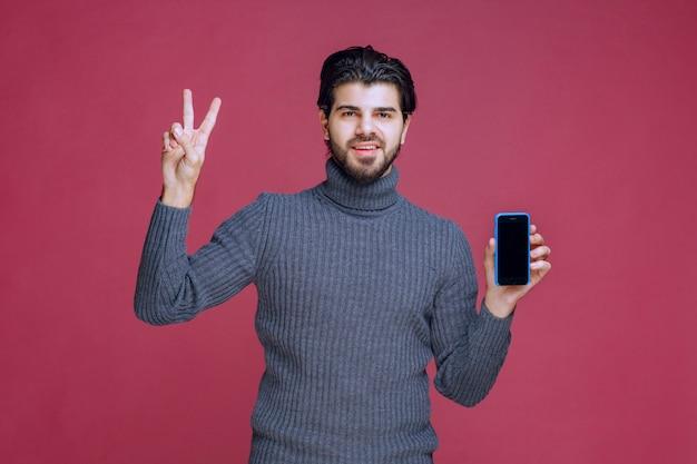 Мужчина держит смартфон и делает знак дружбы.