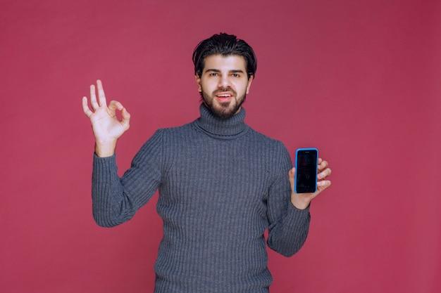 Мужчина держит смартфон и делает хороший знак рукой.
