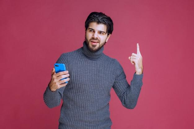 Мужчина держит смартфон и указывает вверх.