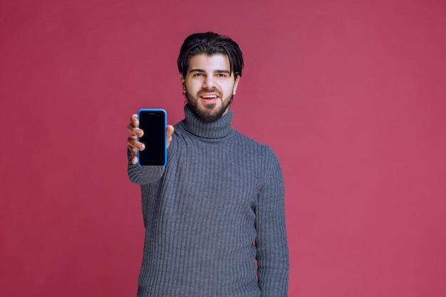 Мужчина держит смартфон и представляет его клиентам. Бесплатные Фотографии