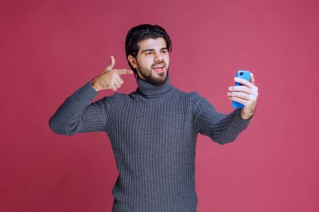 스마트 폰을 들고 화상 통화를하거나 셀카를 찍는 남자.
