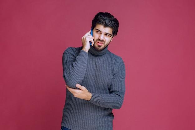 그의 귀에 스마트 폰을 들고 이야기하는 남자.