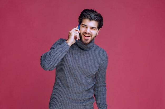 スマートフォンを耳に当てて話している男性。
