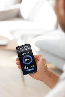 Мужчина держит смартфон с приложением для домашней автоматизации