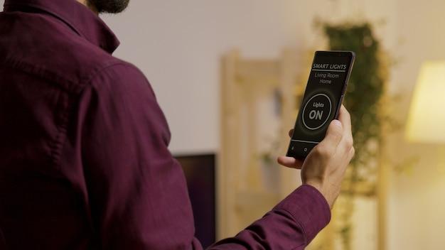 家の照明をつけるための音声起動スマートライトアプリを搭載したスマートフォンを持っている男性。将来のテクノロジーとスマートアプリケーション