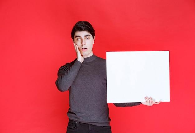 正方形の思考板を持ってブレーンストーミングをしている男