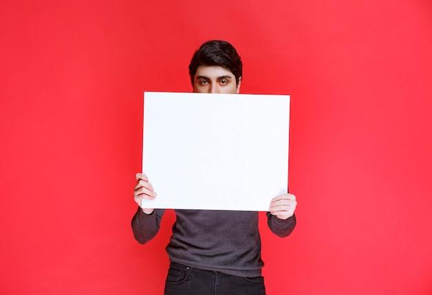 ゲーム用の正方形のthinkboardを保持している男