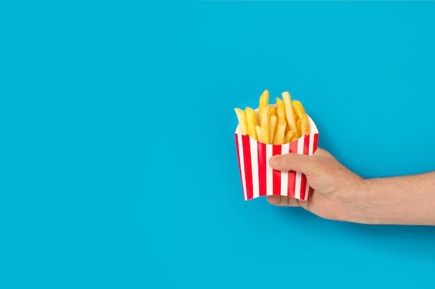 파란색 배경에 감자튀김이 든 줄무늬 상자를 들고 있는 남자