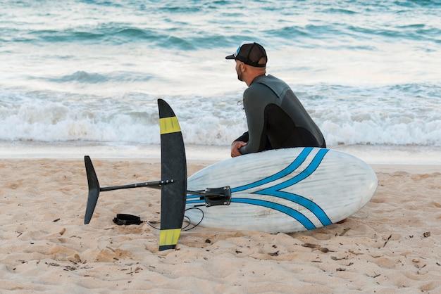 屋外でサーフィンボードを持っている男