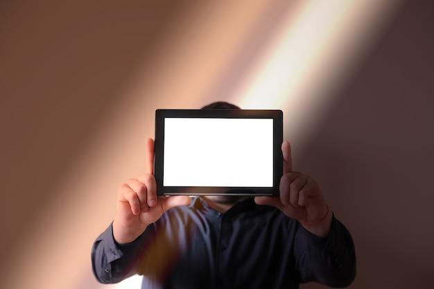 Человек, держащий в руках планшет. экран вместо лица. коммуникация новых технологий.