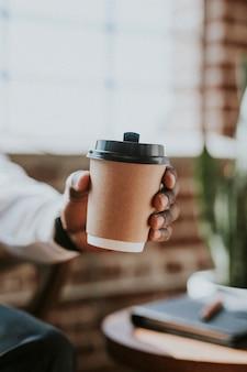 Мужчина держит чашку кофе на вынос