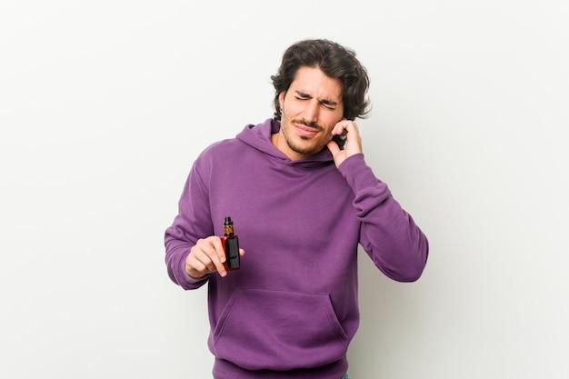 手で耳を覆う気化器を持っている男