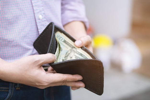 Мужчина держит бумажник с деньгами