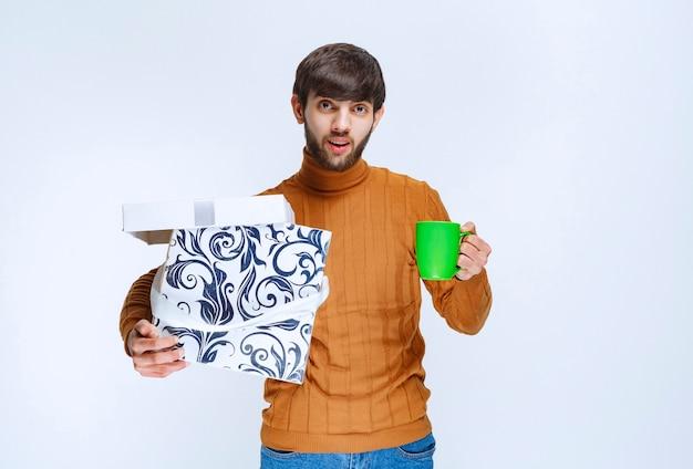 白青のギフトボックスを保持し、満足のコーヒーの緑のカップを持っている男。