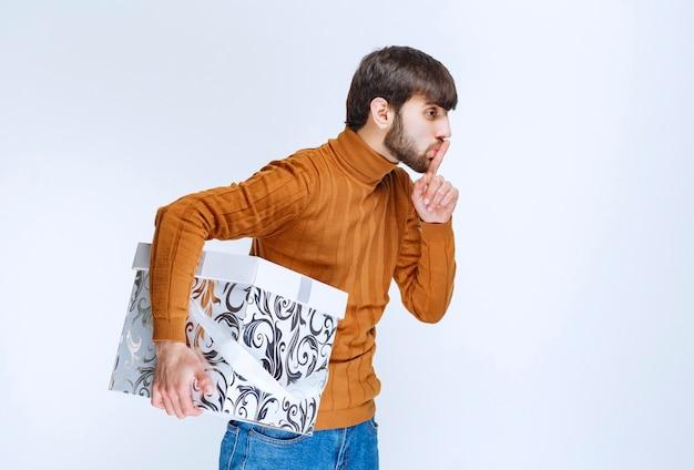 Мужчина держит белую подарочную коробку с синими узорами и просит тишины или колеблется о чем-то.