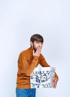 青い模様の白いギフトボックスを持って、沈黙を求めたり、何かをためらったりする男性。