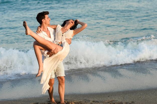 Мужчина держит женщину в белом платье на пляже