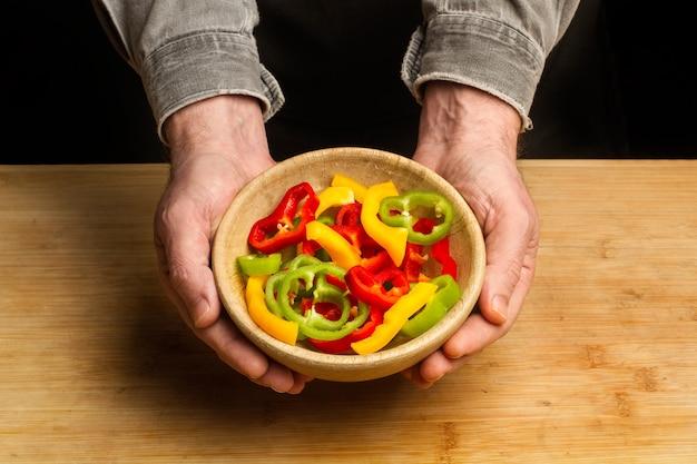 상위 뷰에서 빨강, 녹색 및 노란색 고추 조각으로 나무 그릇을 들고 남자