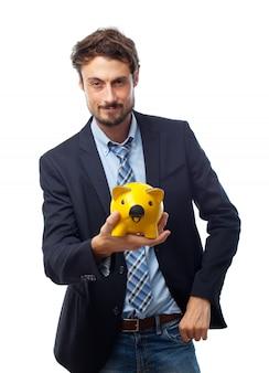 黄色の豚の貯金箱を保持している男